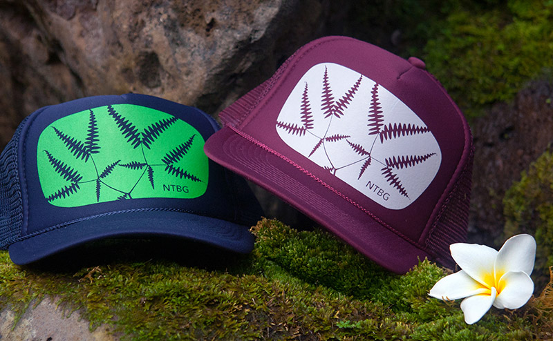 Navy and maroon trucker hats, screenprinted with motifs, resting on mossy rocks.