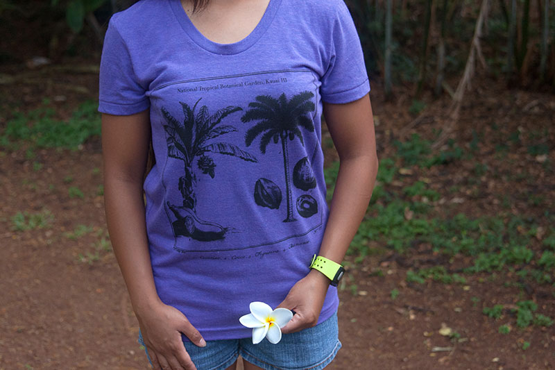 Purple screen print t-shirt on female model holding plumeria.