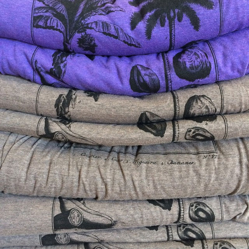 A stack of folded t-shirts, purple on top and brown on bottom.