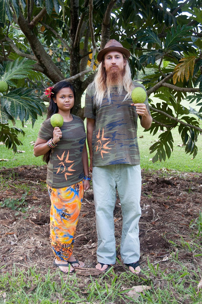 Maegen and David Hubbard modeling screenprint t-shirts in front of a breadfruit tree.